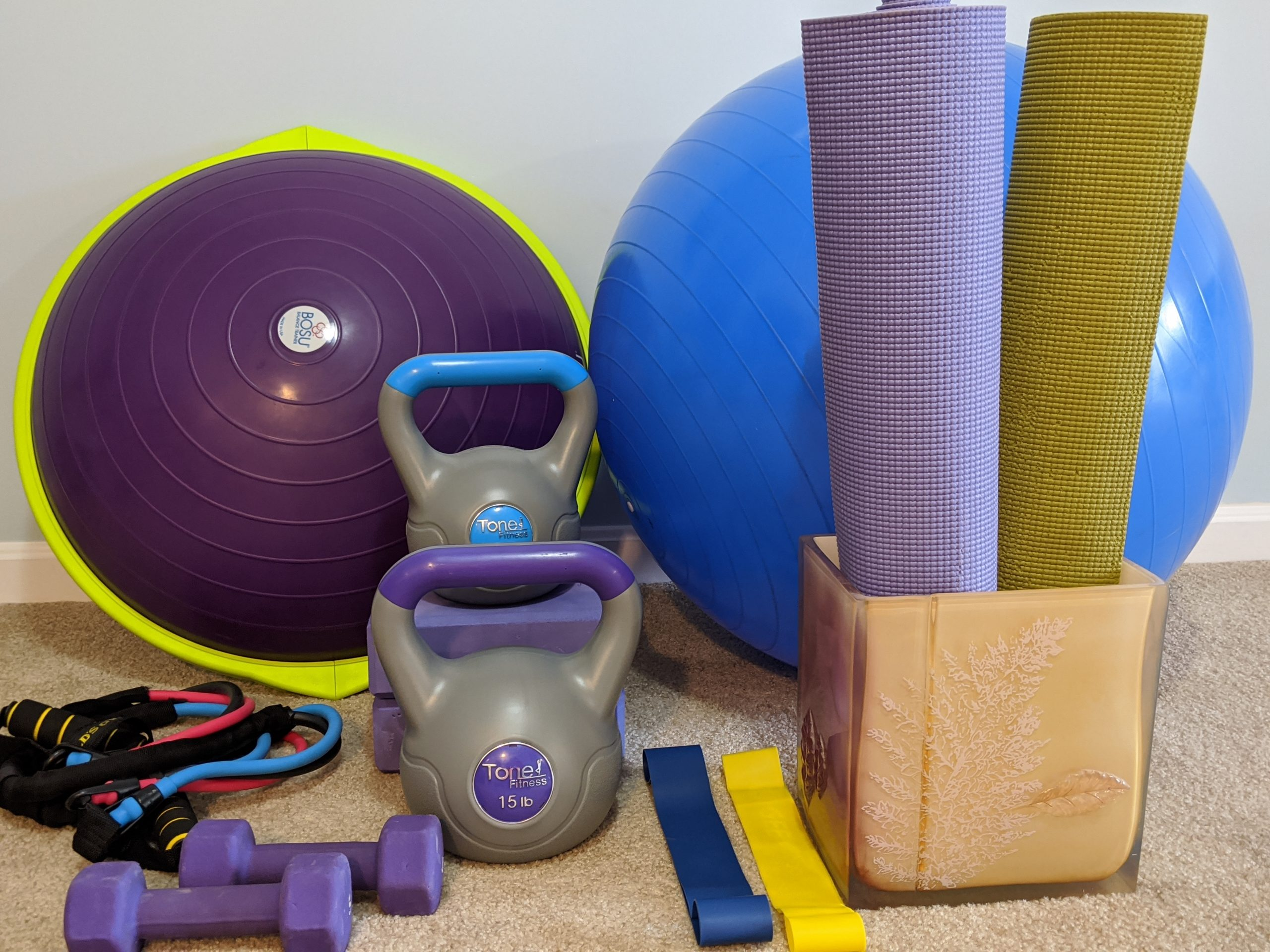 multiple different kinds of exercise equipment laying on the floor such as weights, yoga mats, physioball, resistance bands and bosu ball