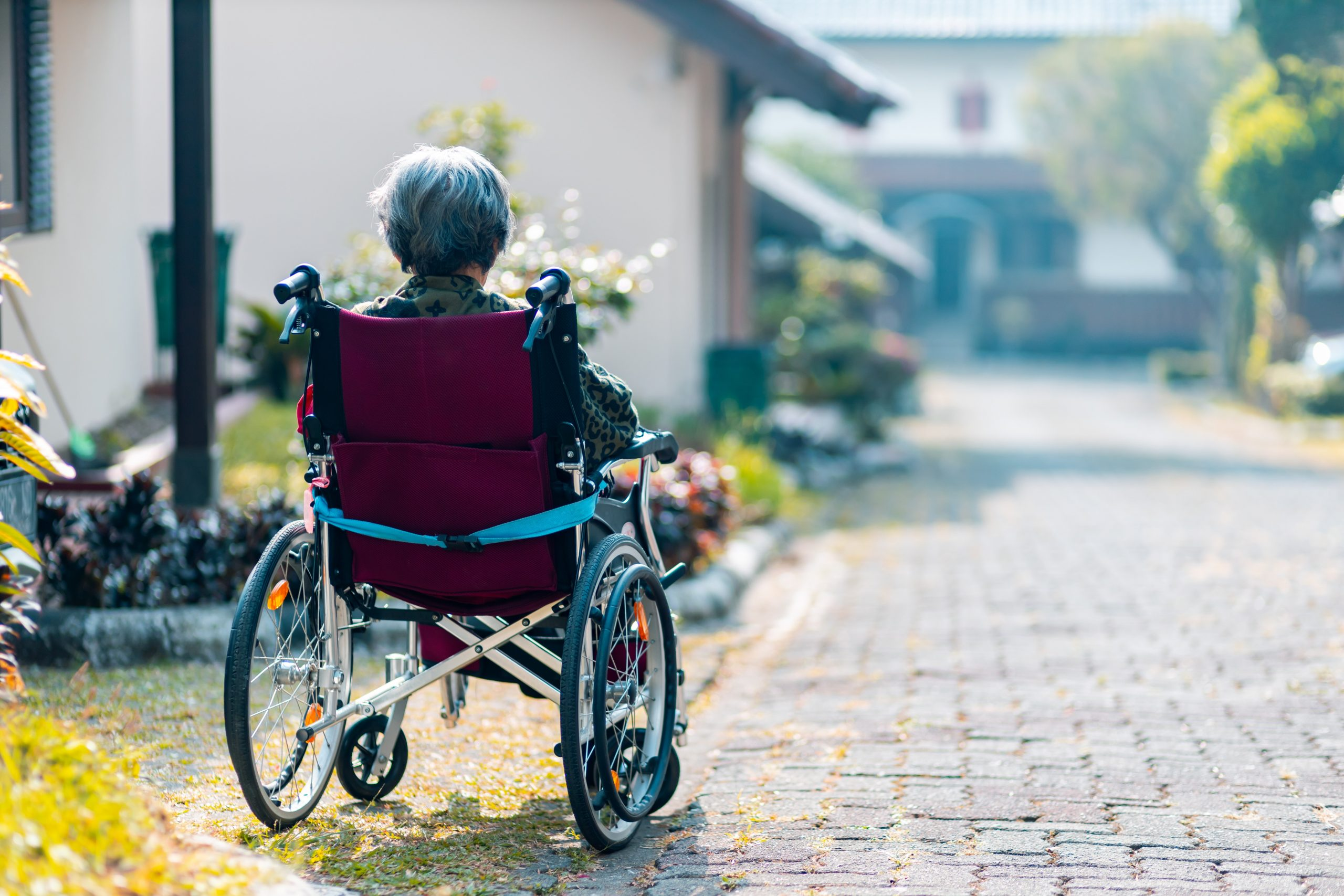 older woman sitting outside in a wheelchair